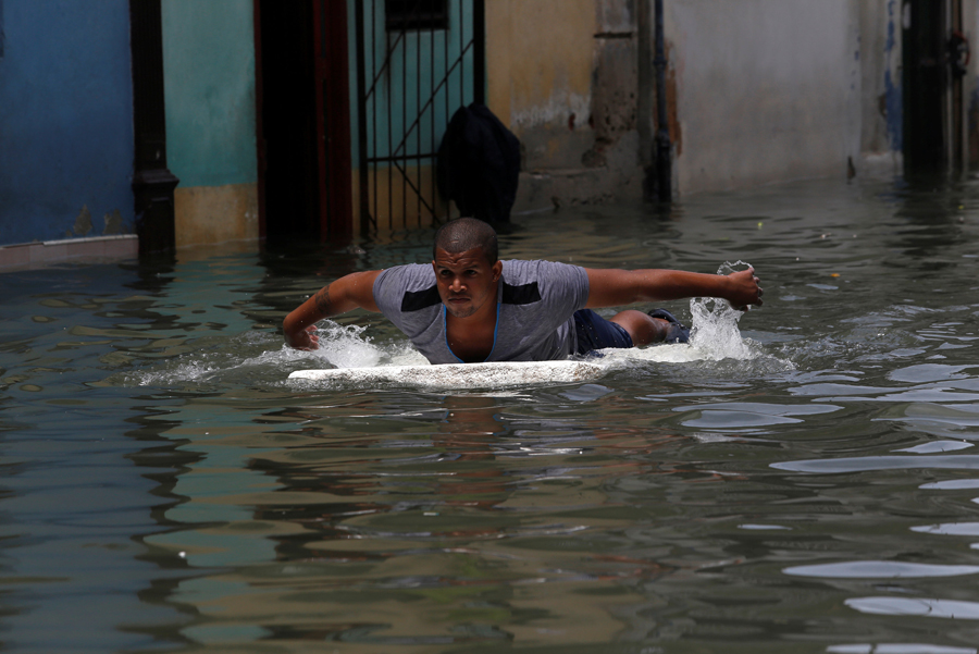 A man uses a piece of foam board to get through a flooded street, after the passing of Hurricane Irma, in Havana, Cuba September 10, 2017. REUTERS/Stringer NO SALES. NO ARCHIVES