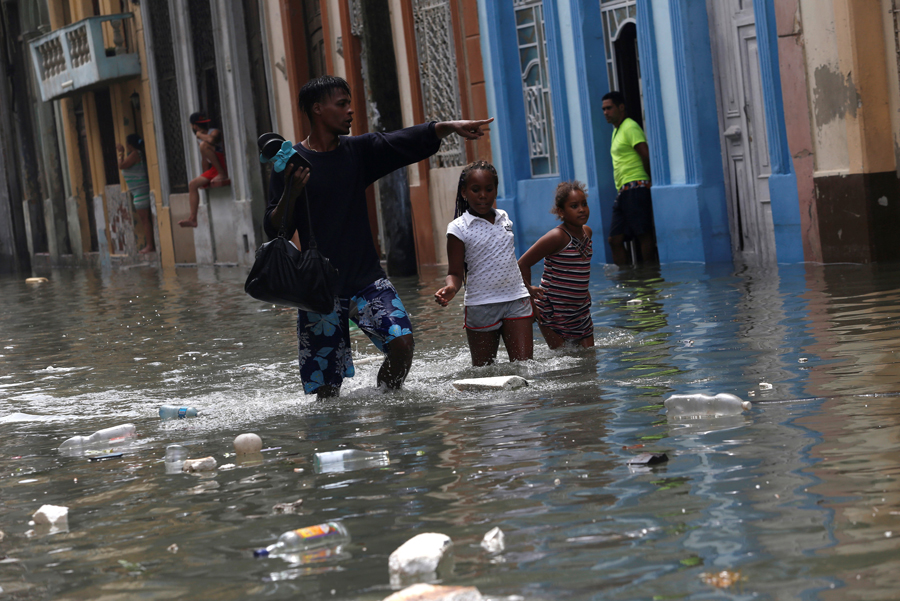 A man and two children wade through a flooded street,  after the passing of Hurricane Irma, in Havana, Cuba September 10, 2017. REUTERS/Stringer NO SALES. NO ARCHIVES