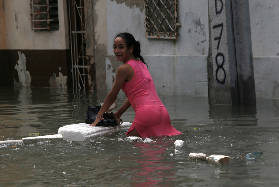 A woman keeps her shoes dry on a piece of foam board while wading through a flooded street, after the passing of Hurricane Irma, in Havana, Cuba September 10, 2017. REUTERS/Stringer NO SALES. NO ARCHIVES