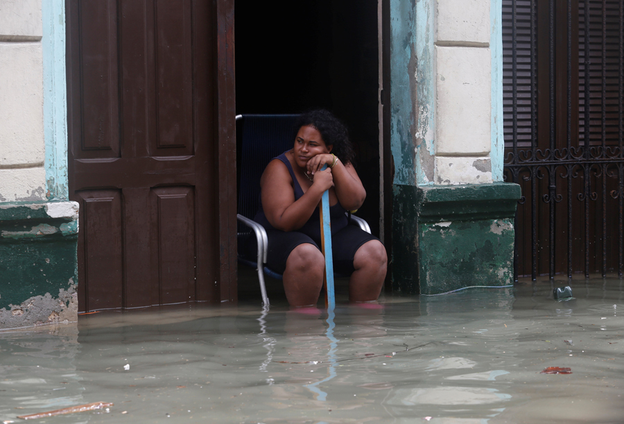 A woman sits in the door of her flooded home, after the passing of Hurricane Irma, in Havana, Cuba September 10, 2017. REUTERS/Stringer NO SALES. NO ARCHIVES