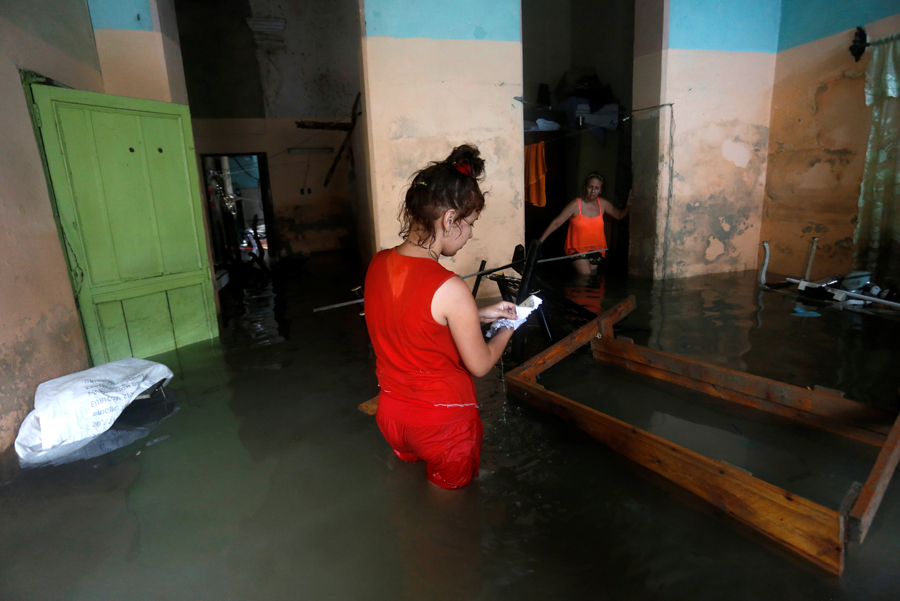 A woman looks at wet papers in her flooded home, after the passing of Hurricane Irma, in Havana, Cuba September 10, 2017. REUTERS/Stringer NO SALES. NO ARCHIVES
