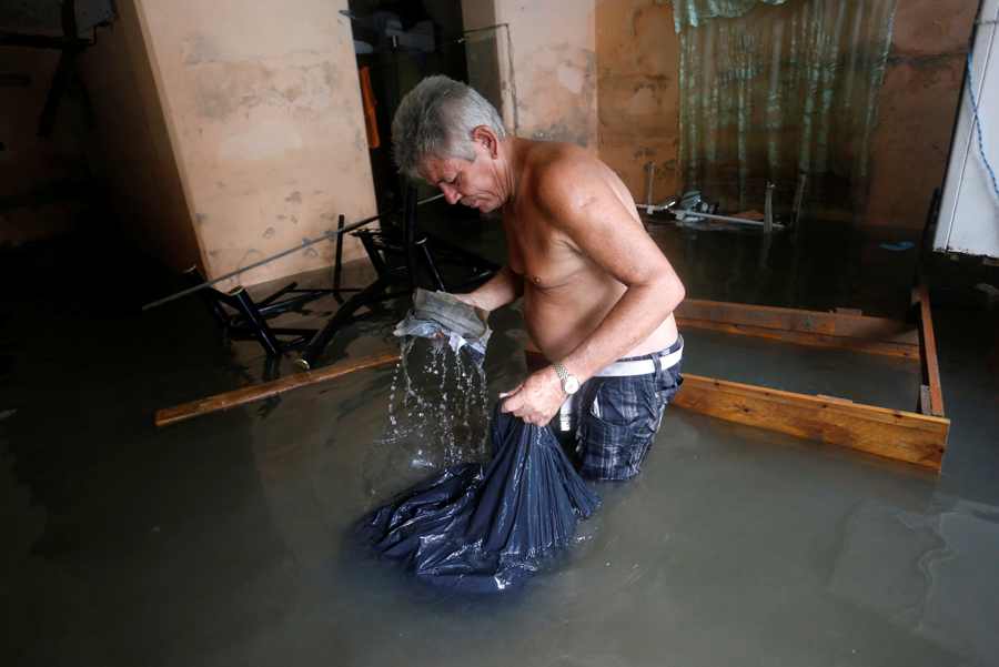 A man picks up spoiled things in his flooded home, after  the passing of Hurricane Irma, in Havana, Cuba September 10, 2017. REUTERS/Stringer NO SALES. NO ARCHIVES