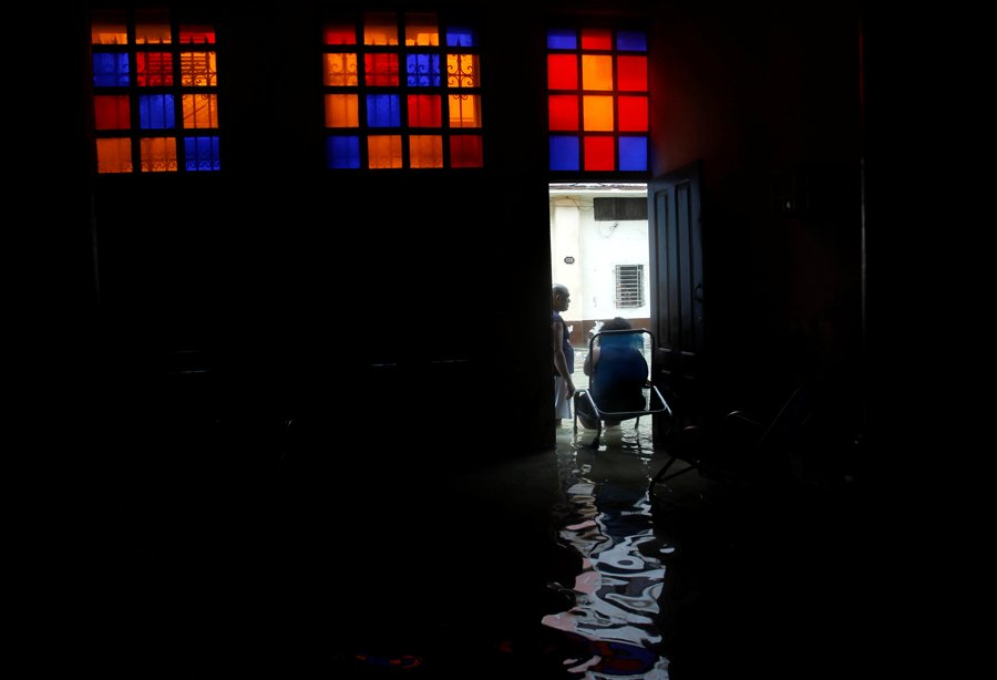 A woman talks to a neighbour while sitting in the door of her flooded home, after the passing of Hurricane Irma, in Havana, Cuba September 10, 2017. REUTERS/Stringer NO SALES. NO ARCHIVES
