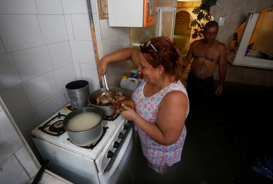 A woman cooks in her flooded home, after the passing of Hurricane Irma, in Havana, Cuba September 10, 2017. REUTERS/Stringer NO SALES. NO ARCHIVES