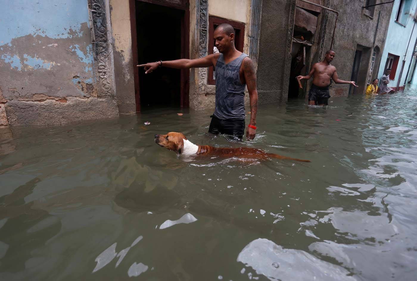 A man gestures to his dog on a flooded street, after the passing of Hurricane Irma, in Havana, Cuba September 10, 2017. REUTERS/Stringer NO SALES. NO ARCHIVES