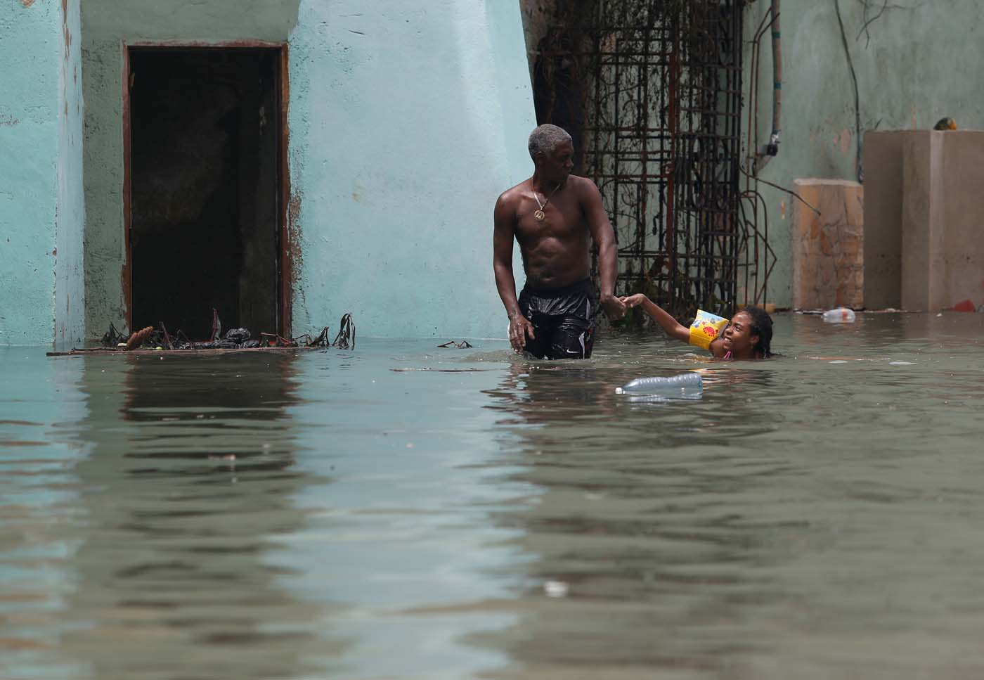A man helps a girl with a swim float as she plays in a flooded street, after the passing of Hurricane Irma, in Havana, Cuba September 10, 2017. REUTERS/Stringer NO SALES. NO ARCHIVES