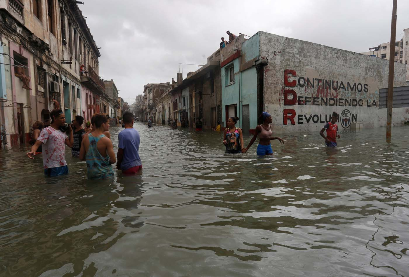 """People wade through a flooded street, after the passing of Hurricane Irma, in Havana, Cuba September 10, 2017. The sign on the wall reads """"We will continue to defend the revolution."""" REUTERS/Stringer NO SALES. NO ARCHIVES"""