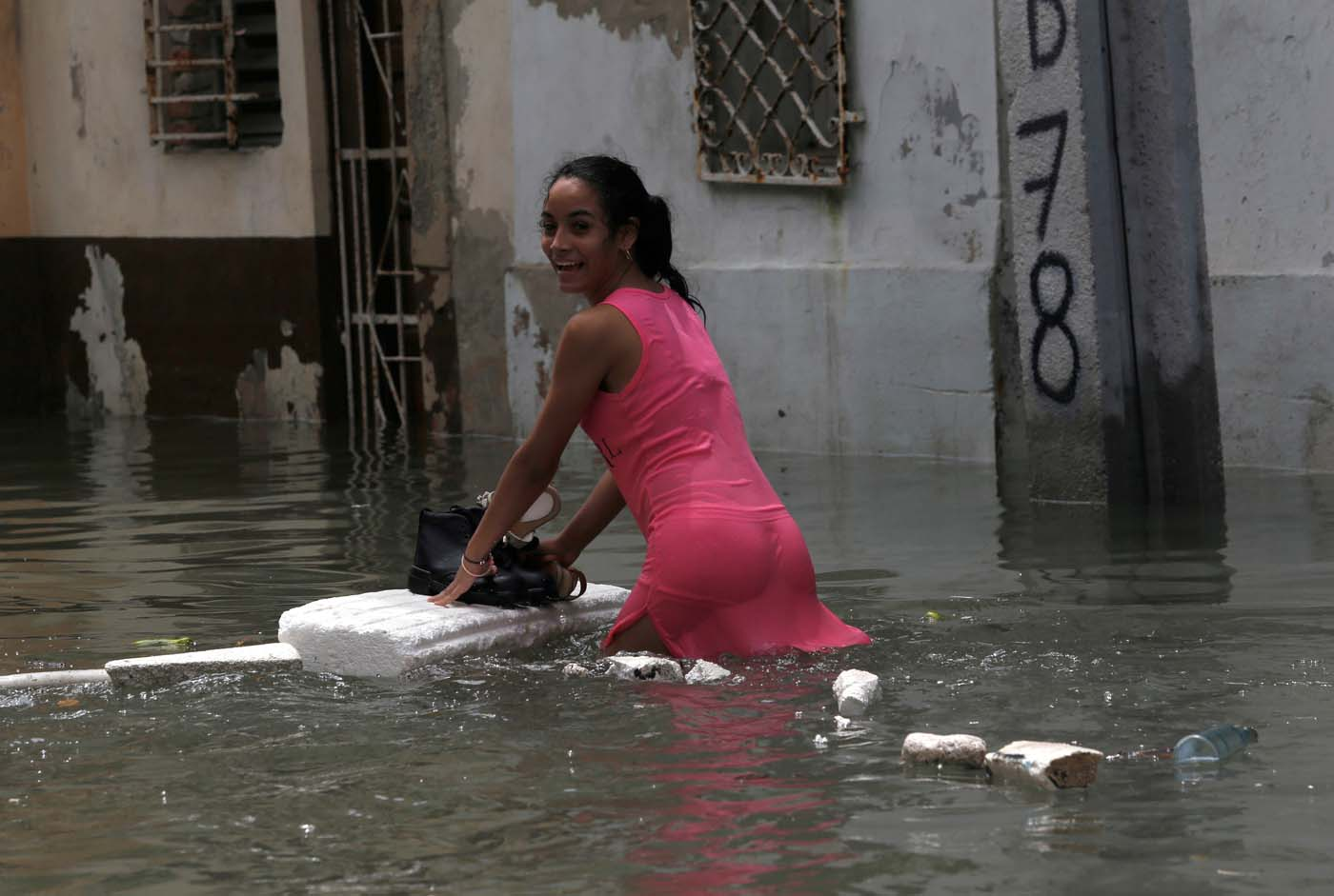 A woman keeps her shoes dry on a piece of foam board while wading through a flooded street, after the passing of Hurricane Irma, in Havana, Cuba September 10, 2017. REUTERS/Stringer NO SALES. NO ARCHIVES TPX IMAGES OF THE DAY