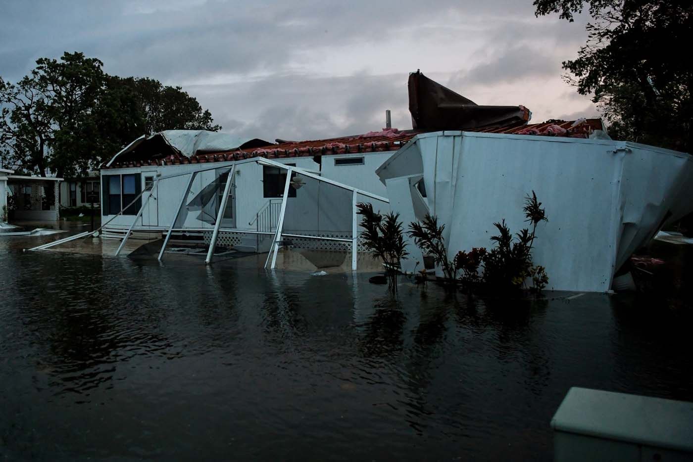 Flood water from Hurricane Irma surround a damaged mobile home in Bonita Springs, Florida, U.S., September 10, 2017. REUTERS/Bryan Woolston