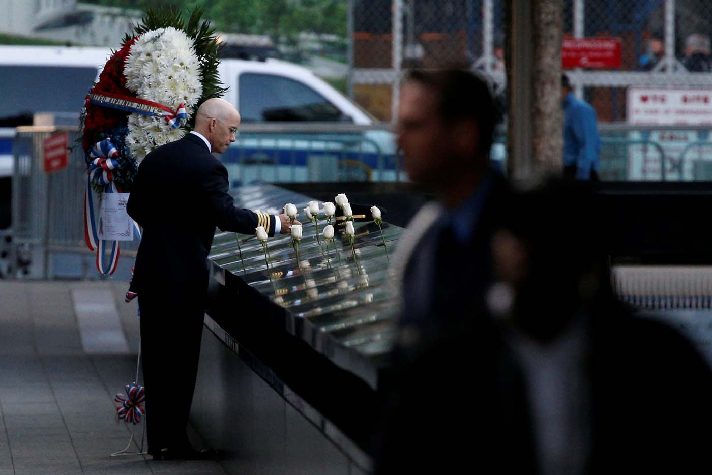 A man places white roses at the edge of the South reflecting pool at the National September 11 Memorial and Museum during ceremonies marking the 16th anniversary of the September 11, 2001 attacks in New York, U.S, September 11, 2017. REUTERS/Brendan McDermid
