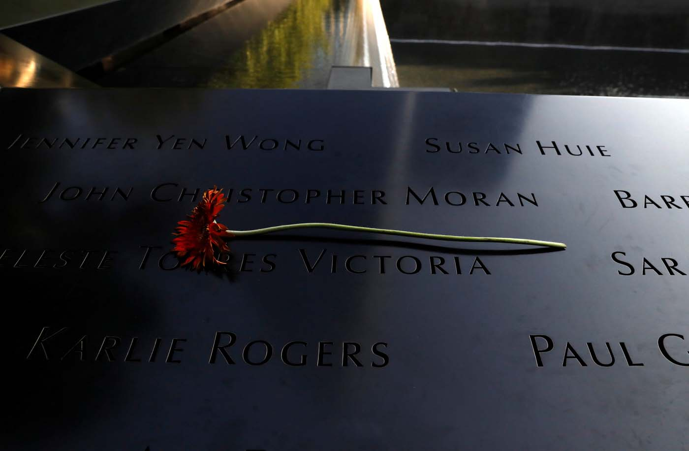 A flower rests over names at the edge of the South reflecting pool at the National September 11 Memorial and Museum during ceremonies marking the 16th anniversary of the September 11, 2001 attacks in New York, U.S. September 11, 2017. REUTERS/Brendan McDermid