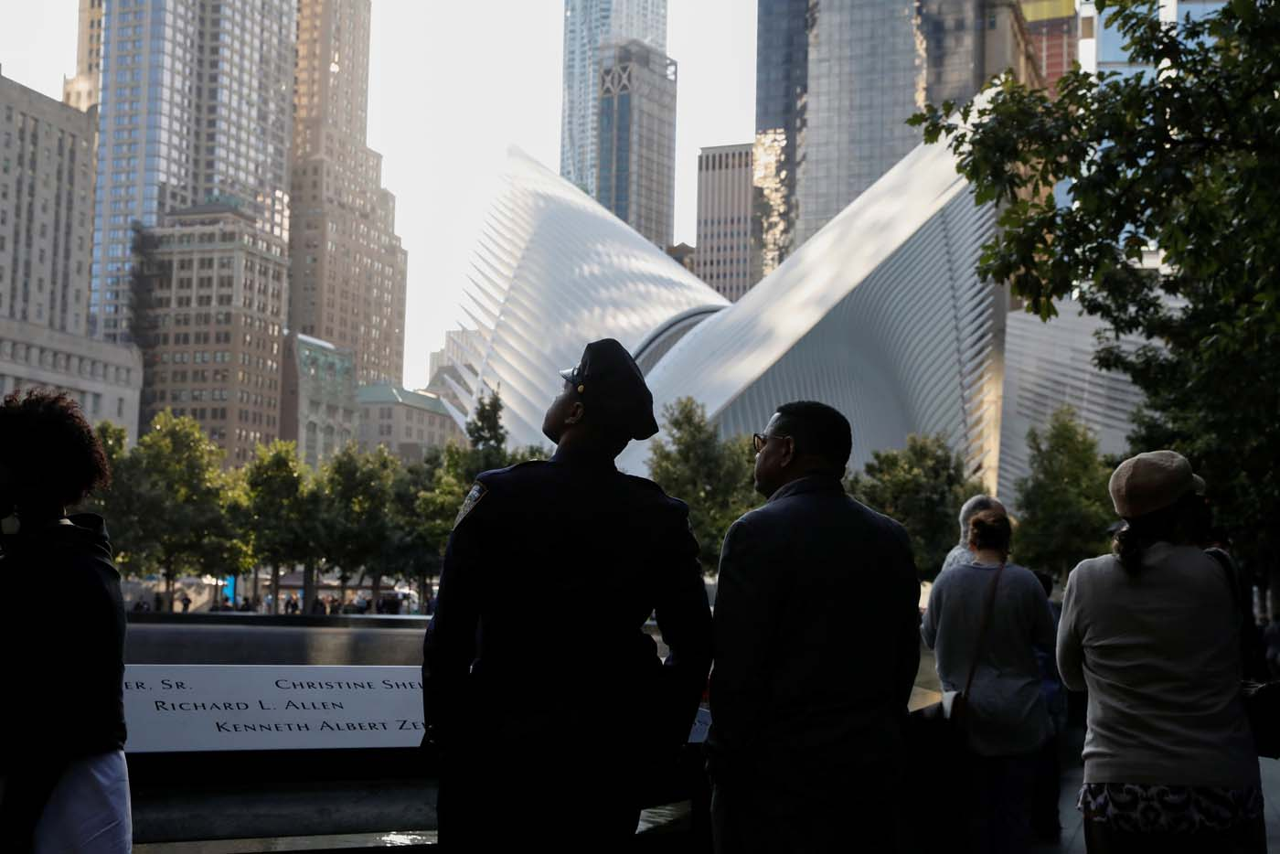 People pause at the edge of the South reflecting pool at the National September 11 Memorial and Museum during ceremonies marking the 16th anniversary of the September 11, 2001 attacks in New York, U.S. September 11, 2017. REUTERS/Brendan McDermid