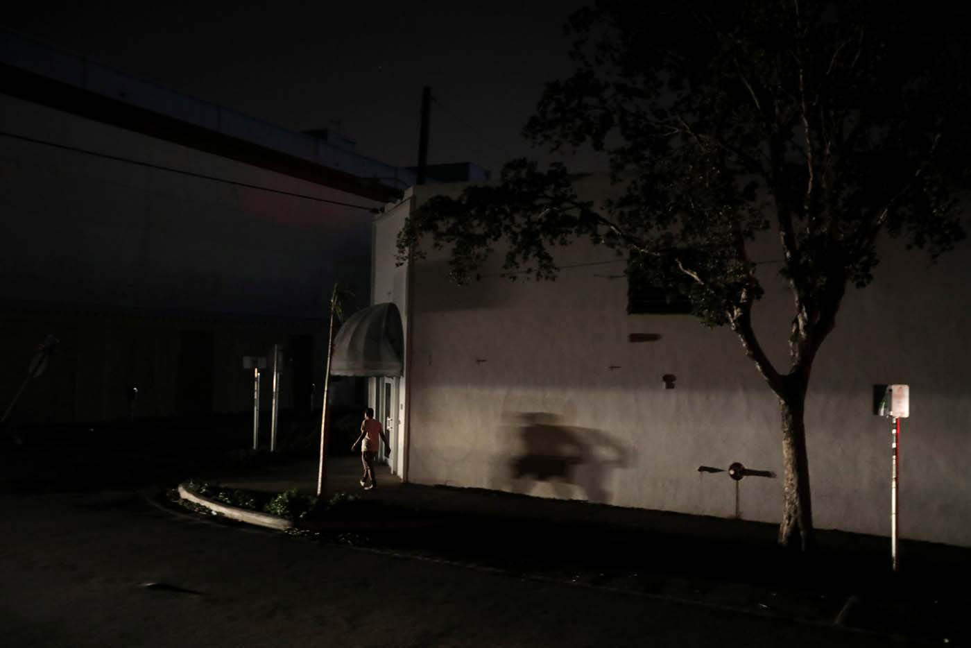 A man walks in the darkness as many areas of Miami still without electricity after Hurricane Irma strikes Florida, in Little Havana, Miami, Florida, September 11, 2017. REUTERS/Carlos Barria