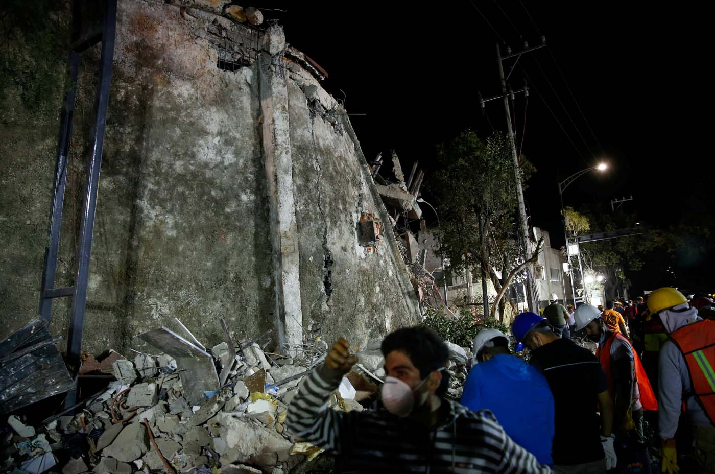 REFILE - REMOVING TYPO - Rescuers walk past a collapsed building after an earthquake in Mexico City, Mexico September 20, 2017. REUTERS/Henry Romero