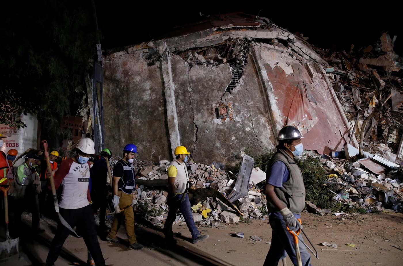 REFILE - REMOVING TYPO - Workers walk past a collapsed building after an earthquake in Mexico City, Mexico September 20, 2017. REUTERS/Henry Romero