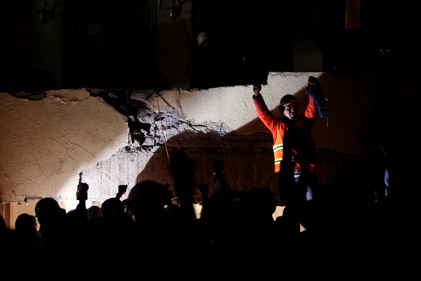 Rescue workers make a silent gesture as they search through rubble during a floodlit search for students at Enrique Rebsamen school in Mexico City, Mexico September 19, 2017. Picture taken September 19, 2017. REUTERS/Carlos Jasso