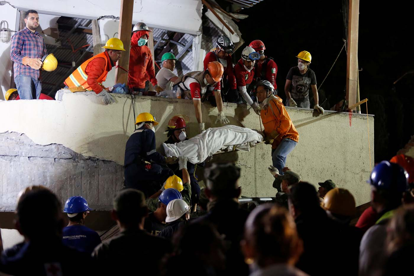 Rescue workers remove a dead body after searching through rubble in a floodlit search for students at Enrique Rebsamen school in Mexico City, Mexico September 20, 2017. REUTERS/Carlos Jasso