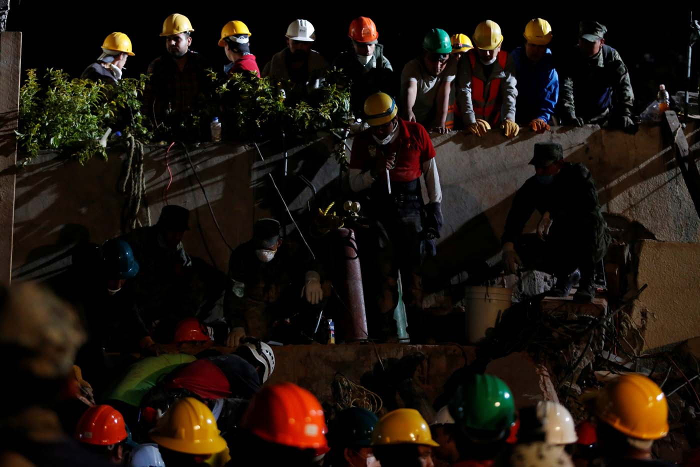 Rescue workers search through rubble in a floodlit search for students at Enrique Rebsamen school in Mexico City, Mexico September 20, 2017. REUTERS/Carlos Jasso