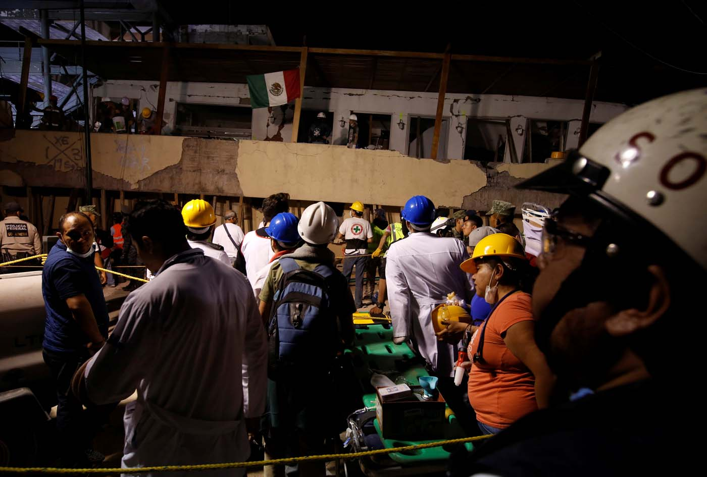 Rescue workers search through rubble in a floodlit search for students at Enrique Rebsamen school in Mexico City, Mexico September 19, 2017. Picture taken on September 19, 2017. REUTERS/Carlos Jasso