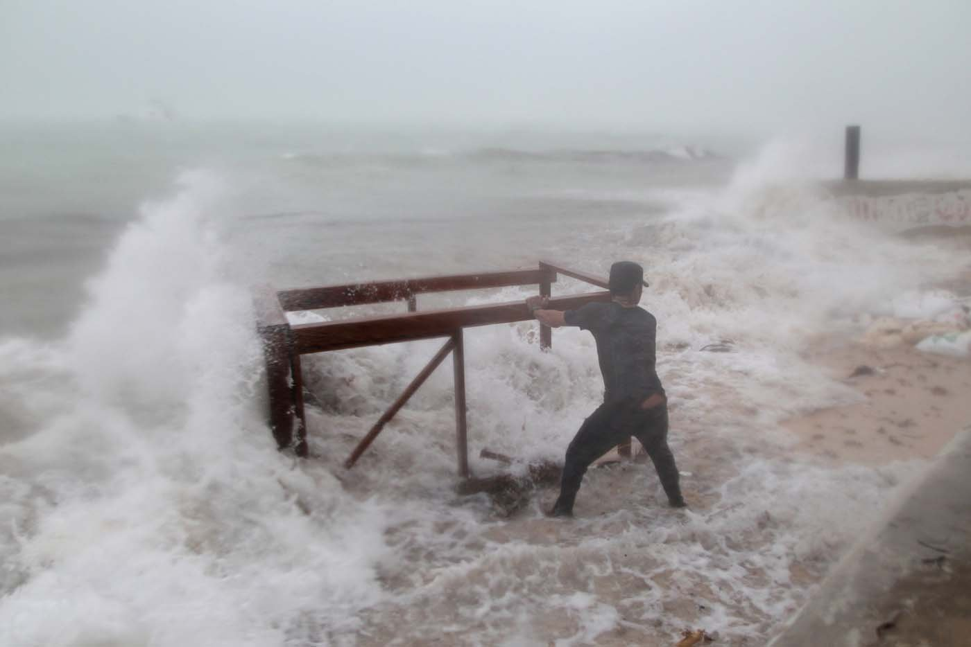 A man tries to salvage a table belonging to his restaurant before the arrival of Hurricane Maria in Punta Cana, Dominican Republic, September 20, 2017. REUTERS/Ricardo Rojas     TPX IMAGES OF THE DAY
