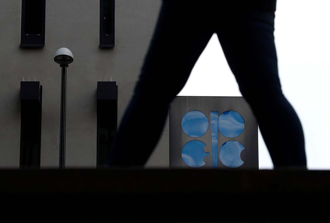 A person passes the logo of the Organization of the Petroleum Exporting Countries (OPEC) in front of its headquarters in Vienna, Austria September 21, 2017. REUTERS/Leonhard Foeger