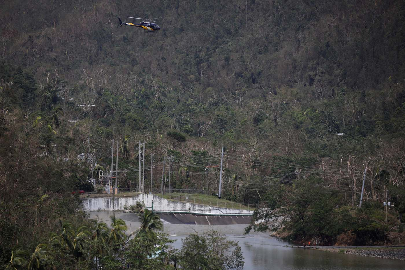 People look at water flowing over the road as a helicopter flies over them at the dam of the Guajataca lake after the area was hit by Hurricane Maria in Guajataca, Puerto Rico September 23, 2017. REUTERS/Carlos Garcia Rawlins
