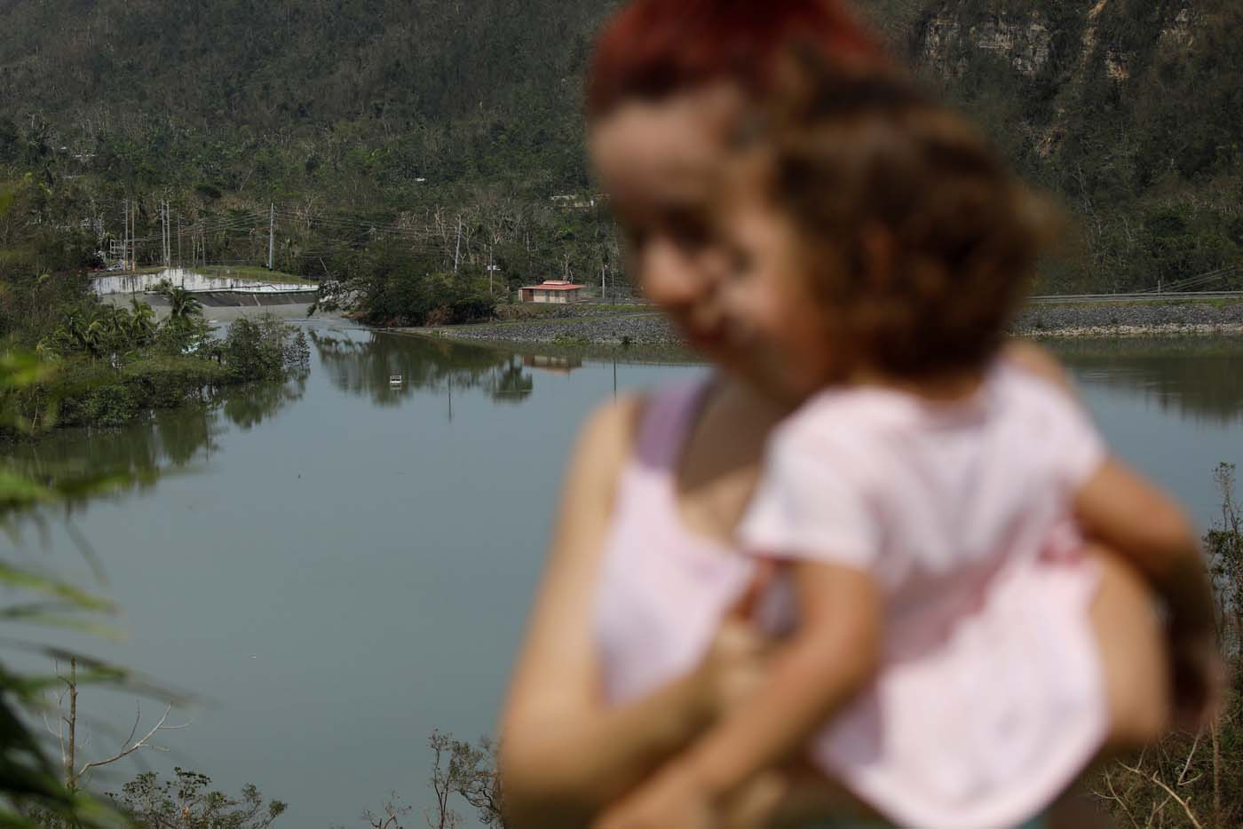 Yadira Nieves carries her daughter as they look at water flowing over the road at the dam of the Guajataca lake after the area was hit by Hurricane Maria in Guajataca, Puerto Rico September 23, 2017. REUTERS/Carlos Garcia Rawlins