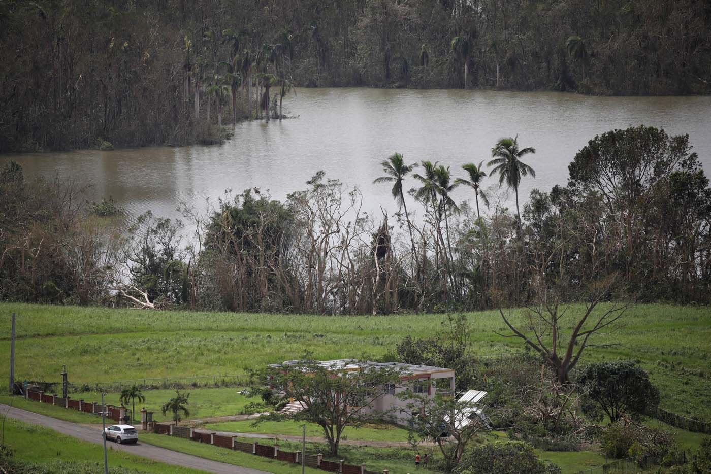 A car drives past a damaged house next to the Guajataca lake after the area was hit by Hurricane Maria in Guajataca, Puerto Rico September 23, 2017. REUTERS/Carlos Garcia Rawlins