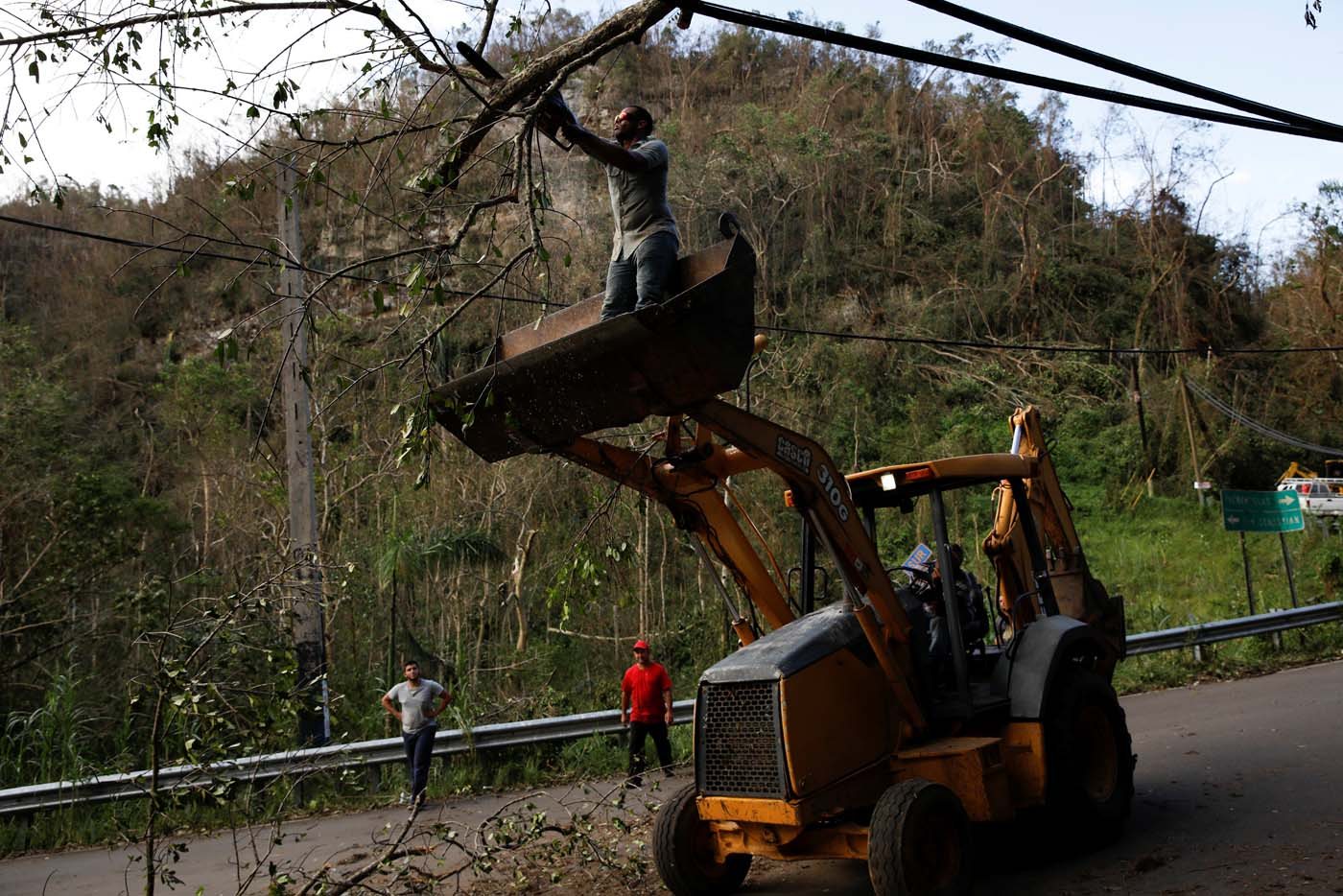 A worker standing on a backhoe loader uses a chainsaw to remove fallen trees from the street after the area was hit by Hurricane Maria in Camuy, Puerto Rico September 23, 2017. REUTERS/Carlos Garcia Rawlins