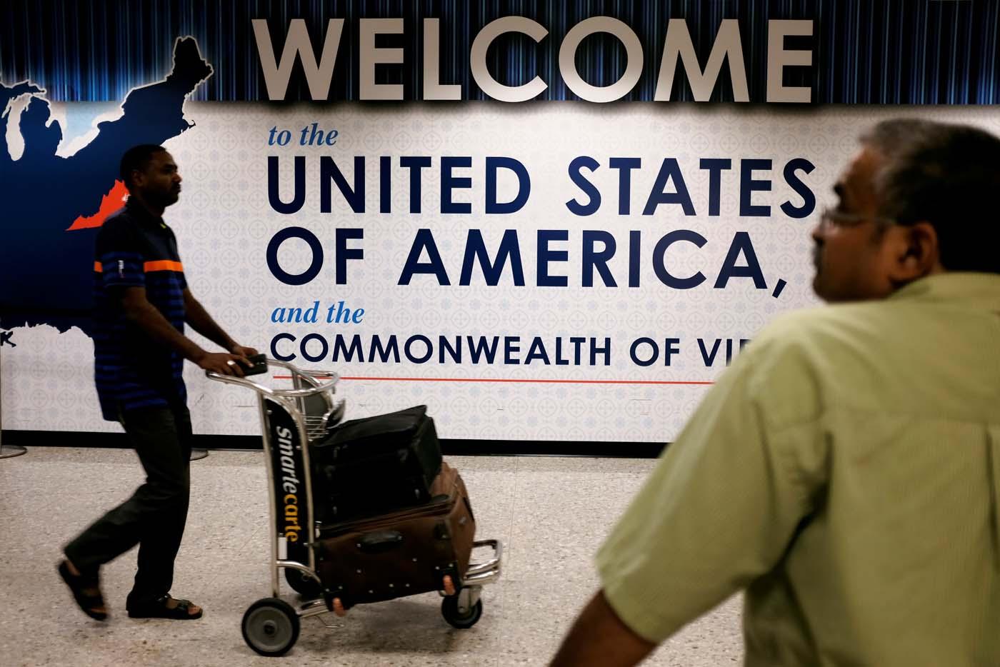 Un pasajero llega al aeropuerto internacional de Dulles mientras una persona espera en el área de arribos en Dulles, Virginia, EEUU. 24 de septiembre, 2017. REUTERS/James Lawler Duggan
