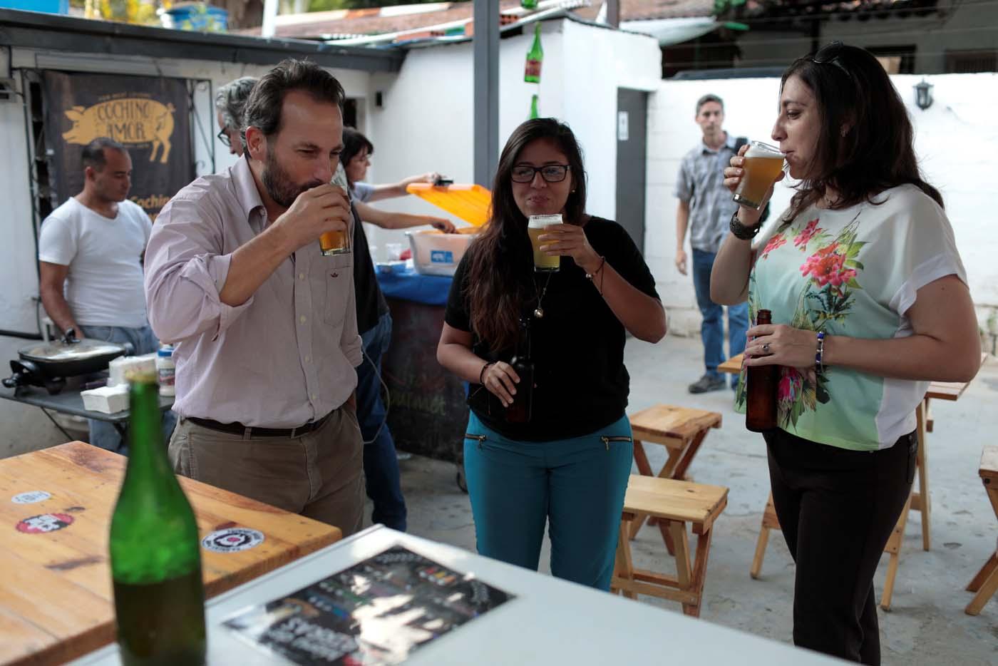 People drink craft beer in a beer garden at the garage of Social Club brewery in Caracas, Venezuela, September 15, 2017. Picture taken September 15, 2017. REUTERS/Marco Bello