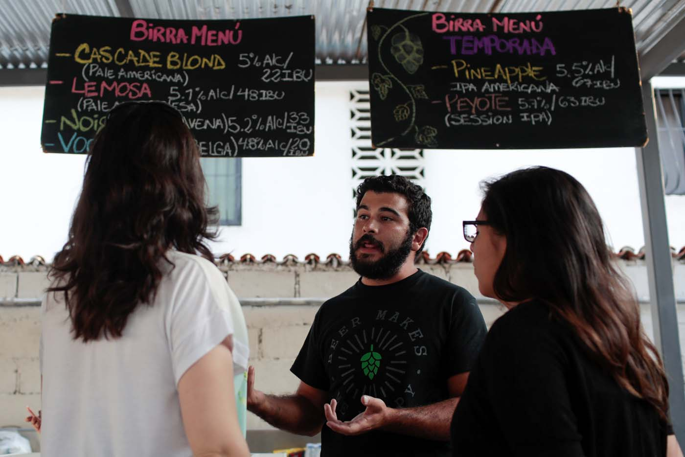 Victor Querales (C), one of the owners of Social Club brewery, explains to customers the variety of craft beers on offer in a beer garden at the garage of his brewery in Caracas, Venezuela September 15, 2017. Picture taken September 15, 2017. REUTERS/Marco Bello