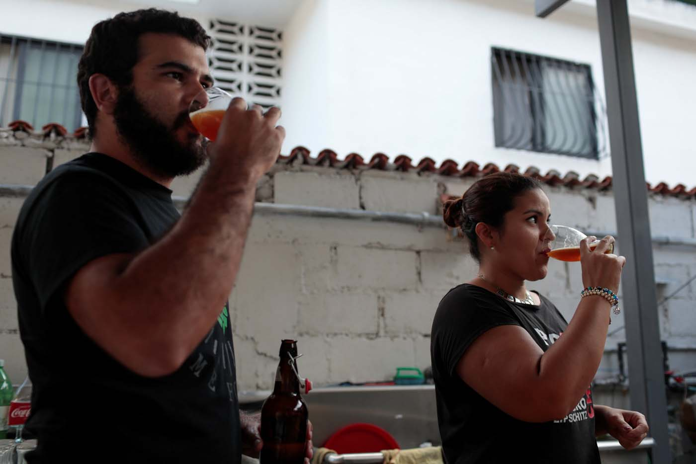 Victor Querales (L), one of the owners of Social Club brewery, and a worker drink craft beer in a beer garden at the garage of his brewery in Caracas, Venezuela September 15, 2017. Picture taken September 15, 2017. REUTERS/Marco Bello