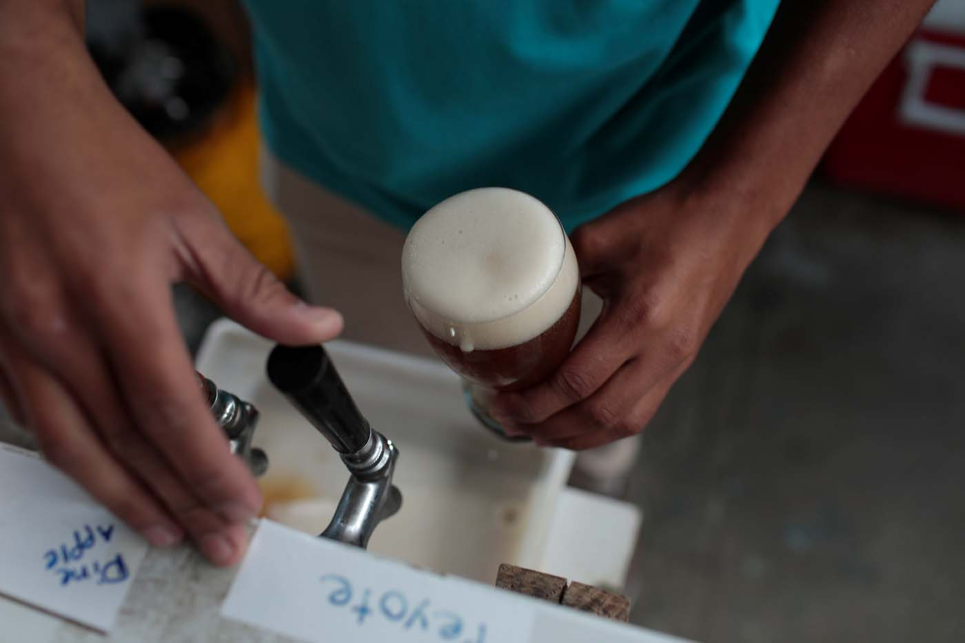 A worker drafts a glass of craft beer from a pump in a beer garden at the garage of Social Club brewery in Caracas, Venezuela, September 15, 2017. Picture taken September 15, 2017. REUTERS/Marco Bello