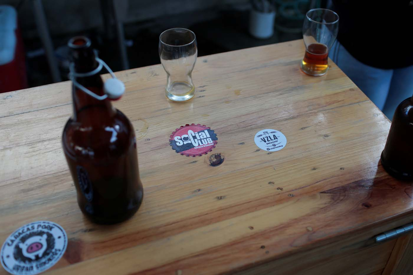 A sticker with the logo of Social Club brewery is seen on a table in a beer garden at the garage of the brewery in Caracas, Venezuela, September 15, 2017. Picture taken September 15, 2017. REUTERS/Marco Bello