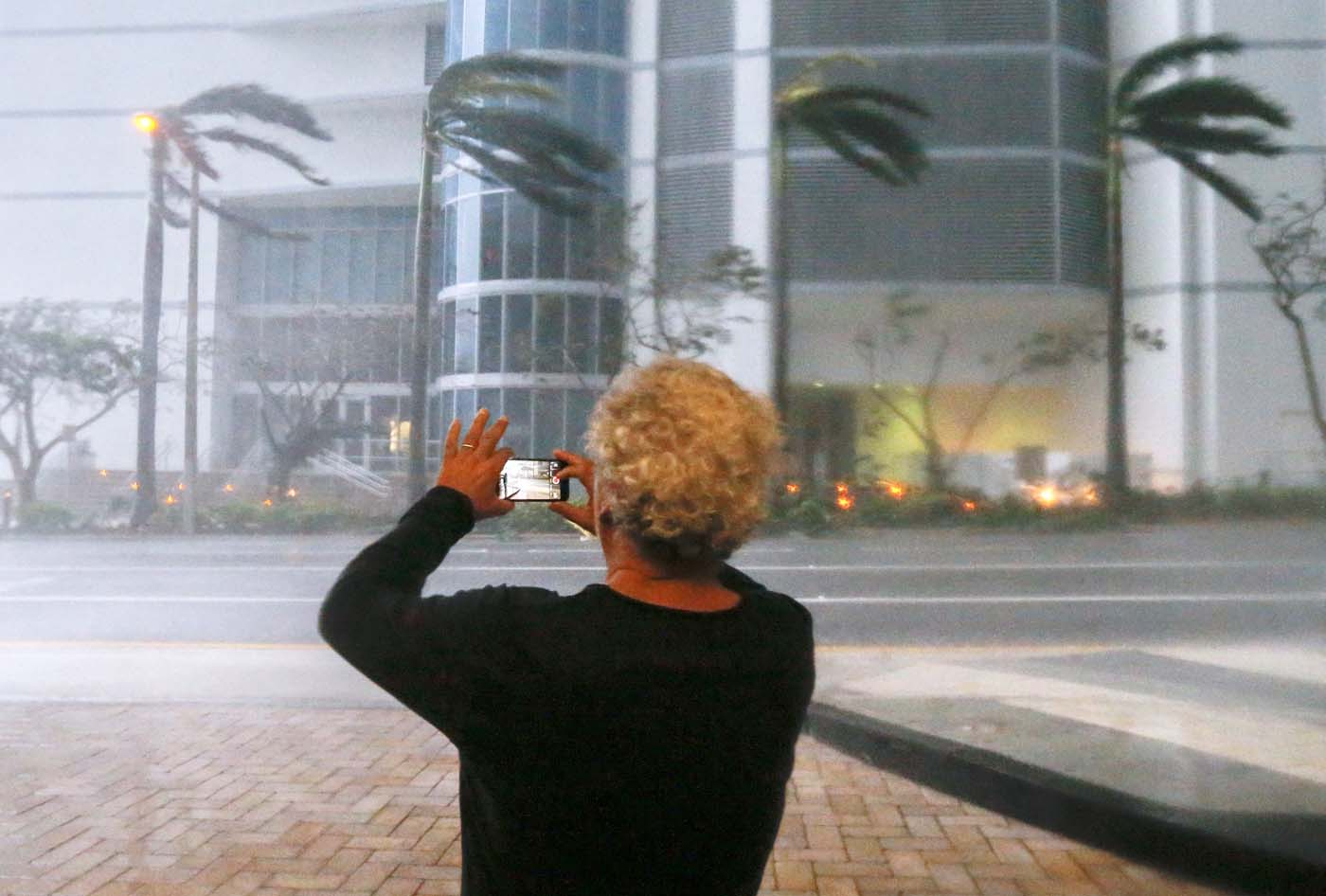 ELX01. Miami (United States), 10/09/2017.- A person photographs the fierce winds with his mobile phone as the full effects of Hurricane Irma strike in Miami, Florida, USA, 10 September 2017. Many areas are under mandatory evacuation orders as Irma approaches Florida. The National Hurricane Center has rated Irma as a Category 4 storm as the eye crosses the lower Florida Keys. (Estados Unidos) EFE/EPA/ERIK S. LESSER
