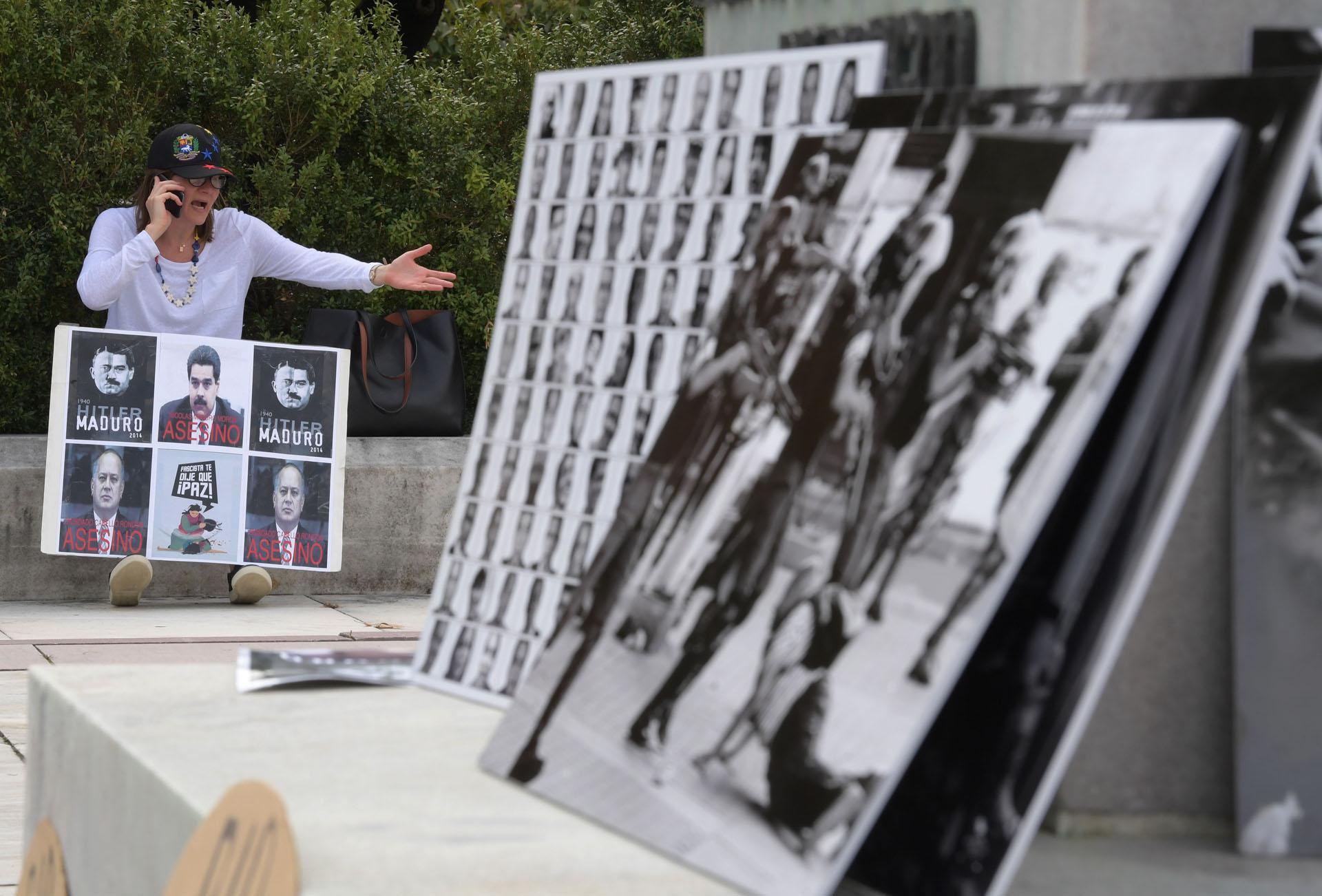 """WAS12. WASHINGTON (DC, EEUU), 14/09/2017.- Una mujer habla por teléfono móvil mientras sostiene una pancarta con unas fotos en las que se lee """"Hitler Maduro; Nicolás Maduro, asesino y Diosdado Cabello Rondón, asesino"""" hoy, jueves 14 de septiembre 2017, frente a la sede de la Organización de los Estados Americanos (OEA) en Washington, DC (EE.UU.). La OEA inició hoy las audiencias públicas en las que se determinará si hay fundamento para denunciar al Gobierno de Venezuela por crímenes de lesa humanidad ante la Corte Penal Internacional (CPI). EFE/Lenin Nolly"""