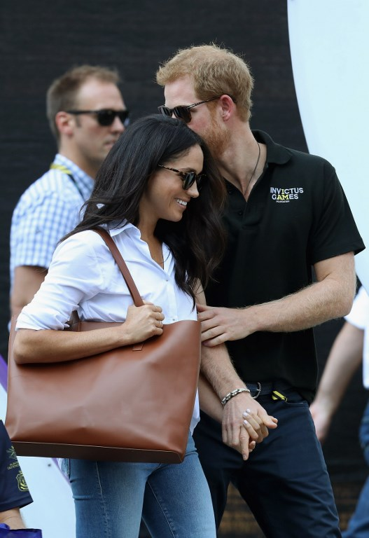 TORONTO, ON - SEPTEMBER 25: Prince Harry (R) and Meghan Markle (L) hold hands a Wheelchair Tennis match during the Invictus Games 2017 at Nathan Philips Square on September 25, 2017 in Toronto, Canada   Chris Jackson/Getty Images for the Invictus Games Foundation /AFP