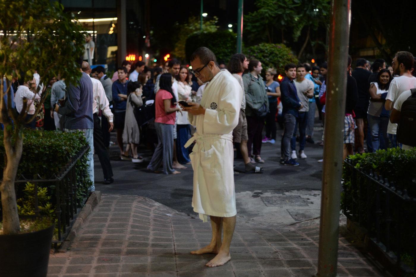 Un grupo de personas se reunen en el centro de la Ciudad de México en los momentos posteriores al terremoto. (AFP PHOTO / Luis PEREZ)