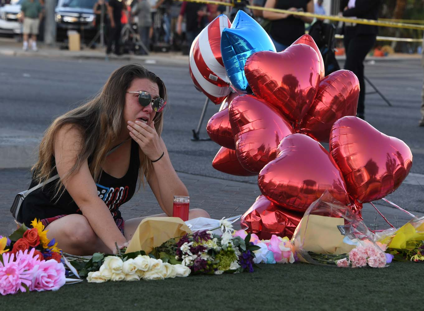 Destiny Alvers who attended the Route 91 country music festival and helped rescue her friend who was shot, reacts at a makeshift memorial on the Las Vegas Strip in Las Vegas, Nevada on October 3, 2017, after a gunman killed 59 people and wounded more than 500 others when he opened fire from a hotel window on a country music festival. Police said the gunman, a 64-year-old local resident named as Stephen Paddock, had been killed after a SWAT team responded to reports of multiple gunfire from the 32nd floor of the Mandalay Bay, a hotel-casino next to the concert venue. / AFP PHOTO / Mark RALSTON