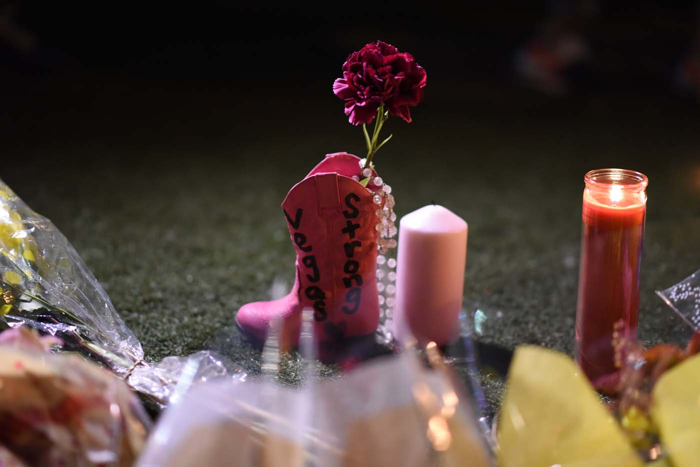 Flowers are placed into a pink boot at a makeshift memorial are seen near the Mandalay Hotel on the Las Vegas Strip, in Las Vegas, Nevada on October 3, 2017, after a gunman killed 58 people and wounded more than 500 others, before taking his own life, when he opened fire from a hotel on a country music festival. Police said the gunman, a 64-year-old local resident named as Stephen Paddock, had been killed after a SWAT team responded to reports of multiple gunfire from the 32nd floor of the Mandalay Bay, a hotel-casino next to the concert venue. / AFP PHOTO / Robyn Beck