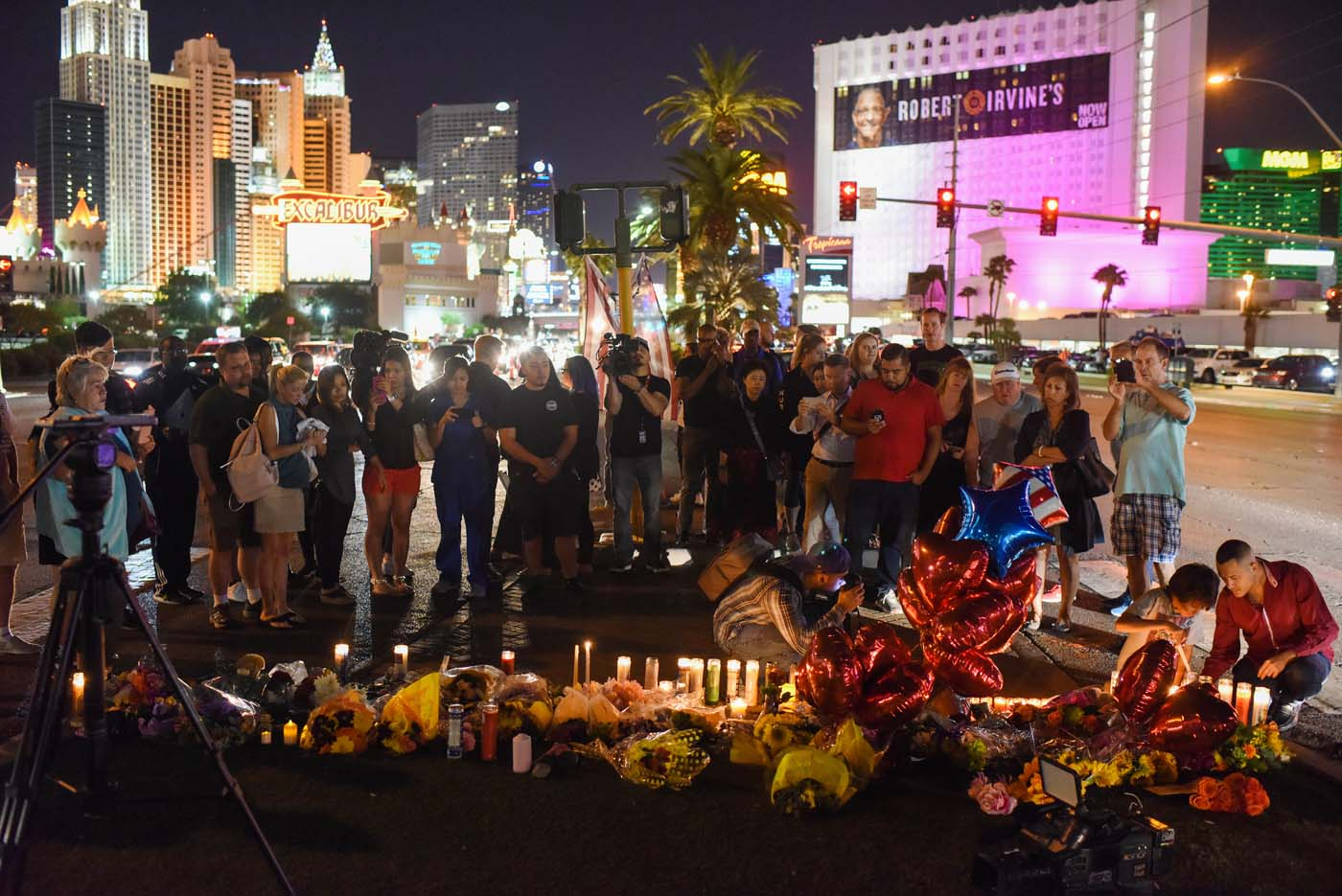 People gather and light candles at a makeshift memorial near the Mandalay Hotel on the Las Vegas Strip, in Las Vegas, Nevada on October 3, 2017, after a gunman killed 58 people and wounded more than 500 others, before taking his own life, when he opened fire from a hotel on a country music festival. Police said the gunman, a 64-year-old local resident named as Stephen Paddock, had been killed after a SWAT team responded to reports of multiple gunfire from the 32nd floor of the Mandalay Bay, a hotel-casino next to the concert venue. / AFP PHOTO / Robyn Beck