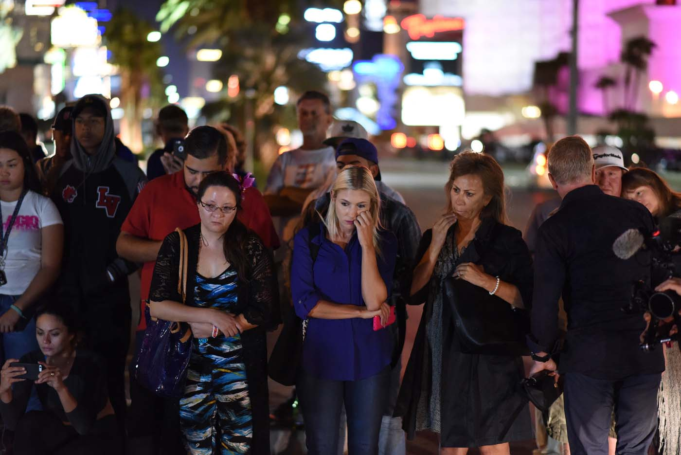 Mourners look on at a makeshift memorial near the Mandalay Hotel on the Las Vegas Strip, in Las Vegas, Nevada on October 3, 2017, after a gunman killed 58 people and wounded more than 500 others, before taking his own life, when he opened fire from a hotel on a country music festival. Police said the gunman, a 64-year-old local resident named as Stephen Paddock, had been killed after a SWAT team responded to reports of multiple gunfire from the 32nd floor of the Mandalay Bay, a hotel-casino next to the concert venue. / AFP PHOTO / Robyn Beck