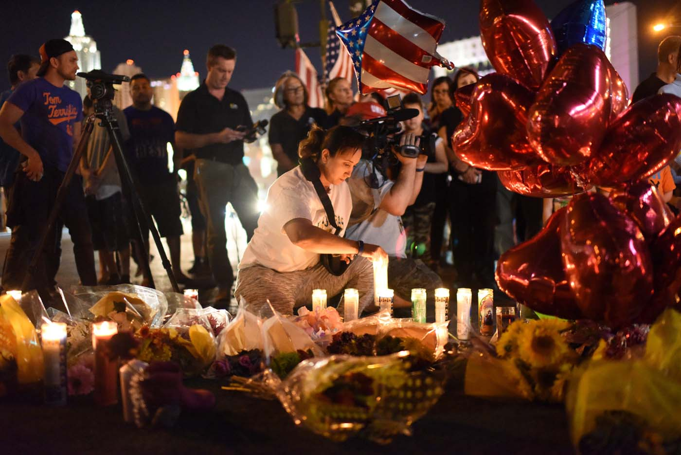 A woman lights a candle at a makeshift memorial near the Mandalay Hotel on the Las Vegas Strip, in Las Vegas, Nevada on October 3, 2017, after a gunman killed 58 people and wounded more than 500 others, before taking his own life, when he opened fire from a hotel on a country music festival. Police said the gunman, a 64-year-old local resident named as Stephen Paddock, had been killed after a SWAT team responded to reports of multiple gunfire from the 32nd floor of the Mandalay Bay, a hotel-casino next to the concert venue. / AFP PHOTO / Robyn Beck