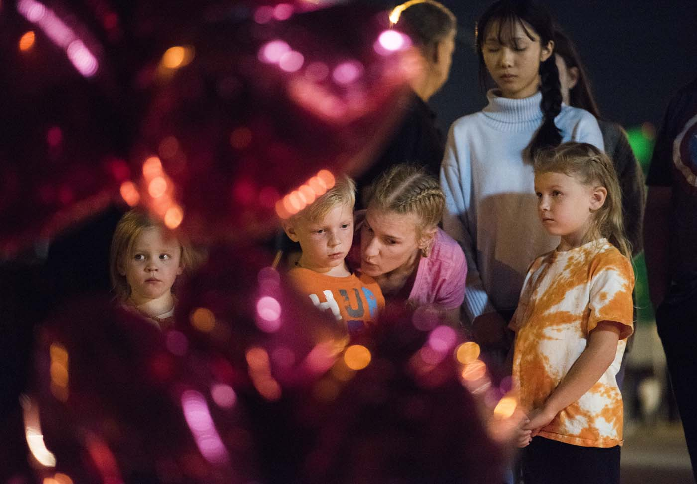 A woman talks with her children at a makeshift memorial near the Mandalay Hotel on the Las Vegas Strip, in Las Vegas, Nevada on October 3, 2017, after a gunman killed 58 people and wounded more than 500 others, before taking his own life, when he opened fire from a hotel on a country music festival. Police said the gunman, a 64-year-old local resident named as Stephen Paddock, had been killed after a SWAT team responded to reports of multiple gunfire from the 32nd floor of the Mandalay Bay, a hotel-casino next to the concert venue. / AFP PHOTO / Robyn Beck