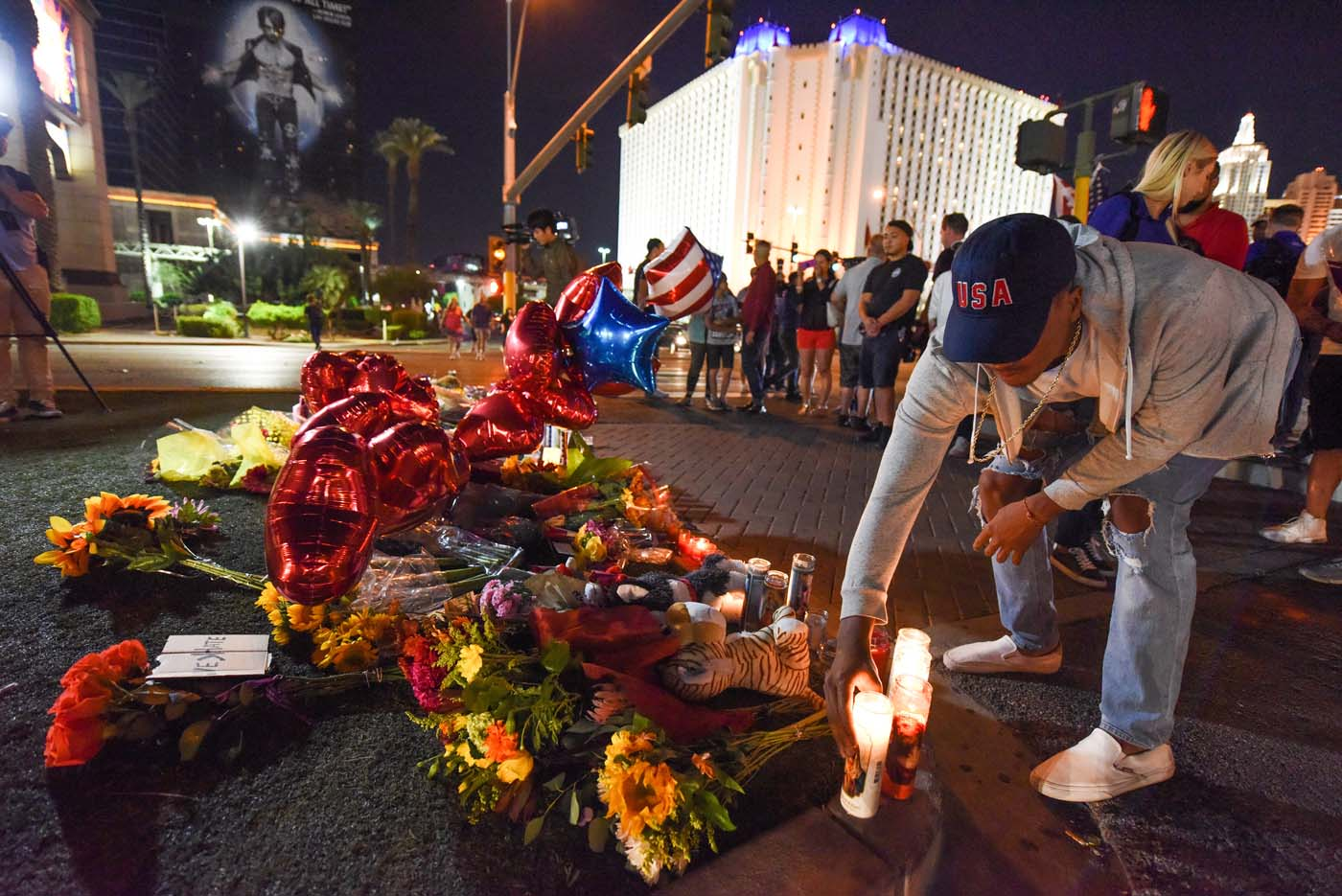 A man places a candle at a makeshift memorial near the Mandalay Hotel on the Las Vegas Strip, in Las Vegas, Nevada on October 3, 2017, after a gunman killed 58 people and wounded more than 500 others, before taking his own life, when he opened fire from a hotel on a country music festival. Police said the gunman, a 64-year-old local resident named as Stephen Paddock, had been killed after a SWAT team responded to reports of multiple gunfire from the 32nd floor of the Mandalay Bay, a hotel-casino next to the concert venue. / AFP PHOTO / Robyn Beck