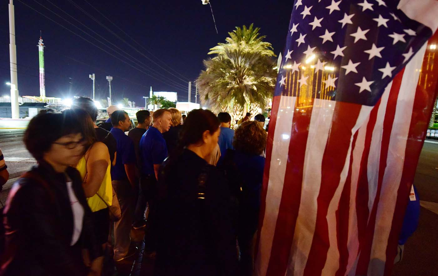 People look on near a US national flag at a makeshift memorial near the Mandalay Hotel on the Las Vegas Strip, in Las Vegas, Nevada on October 3, 2017, after a gunman killed 58 people and wounded more than 500 others, before taking his own life, when he opened fire from a hotel on a country music festival. Police said the gunman, a 64-year-old local resident named as Stephen Paddock, had been killed after a SWAT team responded to reports of multiple gunfire from the 32nd floor of the Mandalay Bay, a hotel-casino next to the concert venue. / AFP PHOTO / Robyn Beck
