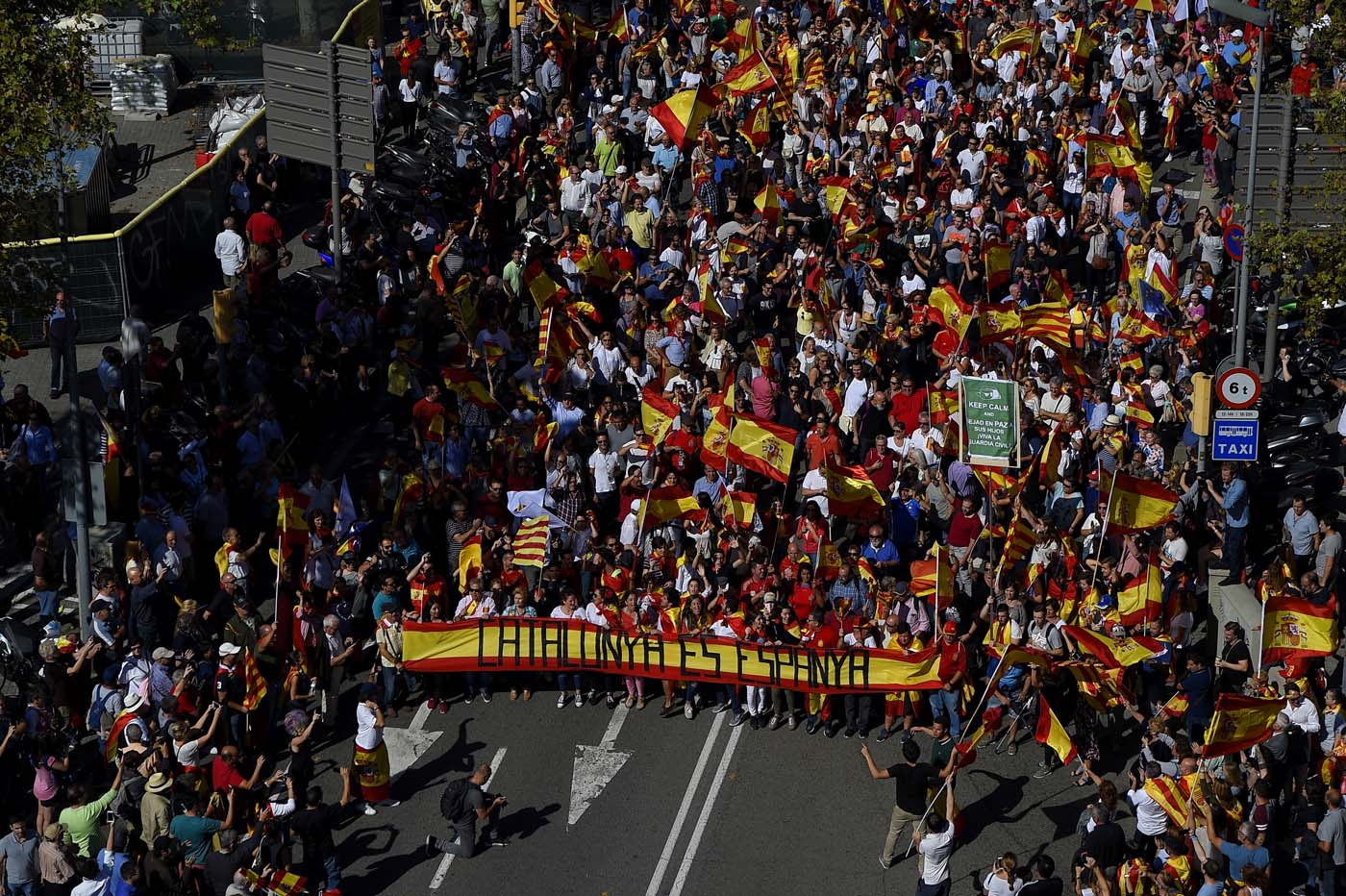 """Protesters hold a giant Spanish flag reading """"Catalonia is Spain"""" during a demonstration called by """"Societat Civil Catalana"""" (Catalan Civil Society) to support the unity of Spain on October 8, 2017 in Barcelona. Spain braced for more protests despite tentative signs that the sides may be seeking to defuse the crisis after Madrid offered a first apology to Catalans injured by police during their outlawed independence vote. / AFP PHOTO / LLUIS GENE"""