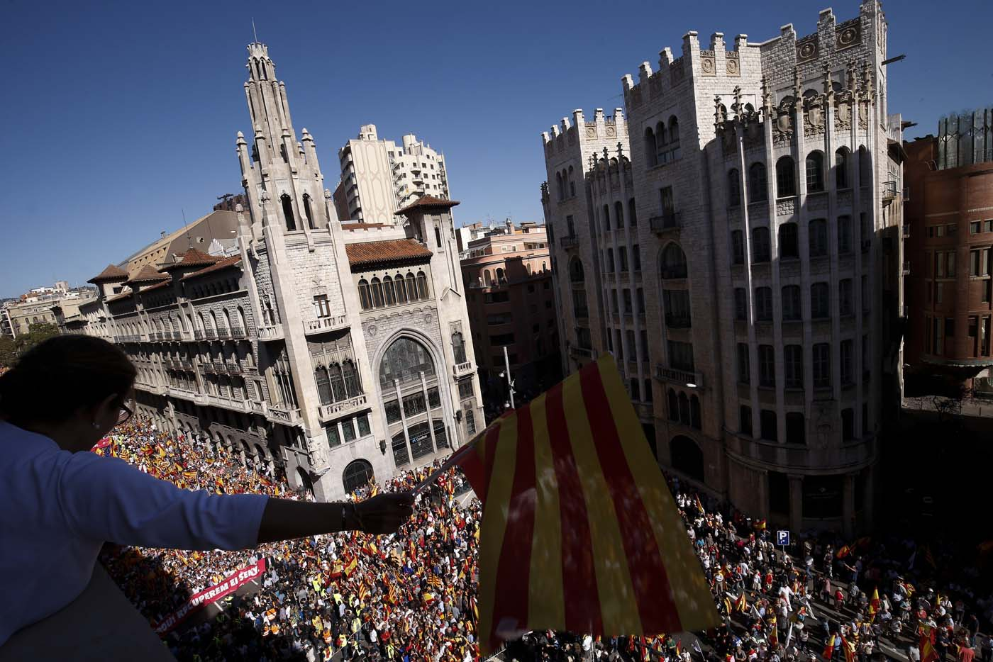 "A protester holds a Catalan flag from a balcony during a demonstration called by ""Societat Civil Catalana"" (Catalan Civil Society) to support the unity of Spain on October 8, 2017 in Barcelona. Spain braced for more protests despite tentative signs that the sides may be seeking to defuse the crisis after Madrid offered a first apology to Catalans injured by police during their outlawed independence vote. / AFP PHOTO / PAU BARRENA"