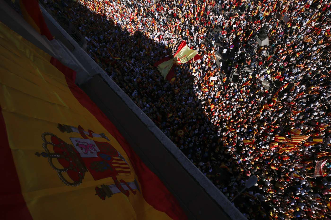 "Protesters hold Spanish and Catalan flags during a demonstration called by ""Societat Civil Catalana"" (Catalan Civil Society) to support the unity of Spain on October 8, 2017 in Barcelona. Spain braced for more protests despite tentative signs that the sides may be seeking to defuse the crisis after Madrid offered a first apology to Catalans injured by police during their outlawed independence vote. / AFP PHOTO / PAU BARRENA"